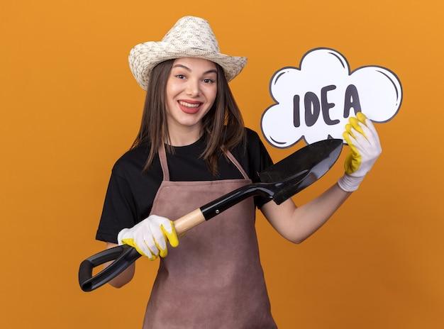 Souriante jolie jardinière caucasienne portant un chapeau de jardinage et des gants tenant et pointant sur une bulle d'idée avec une pelle
