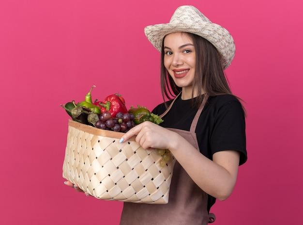 Souriante jolie jardinière caucasienne portant chapeau de jardinage tenant un panier de légumes regardant la caméra sur rose
