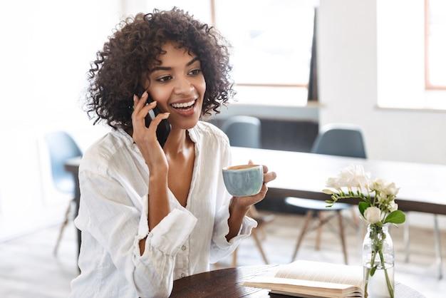 Souriante jolie jeune femme africaine se détendre à l'intérieur, à l'aide de téléphone portable, parler