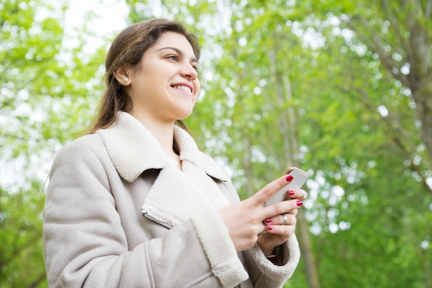 Souriante jolie jeune femme à l'aide de smartphone dans le parc