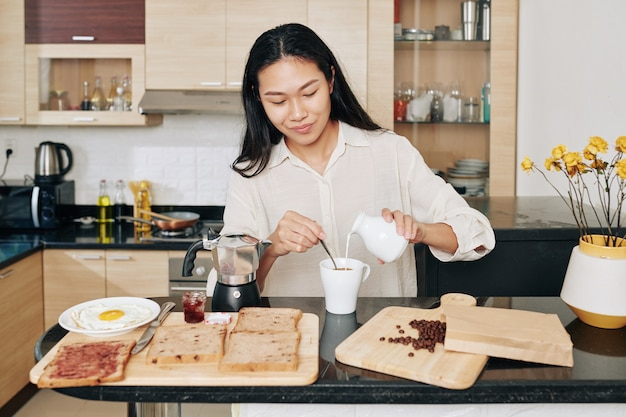 Souriante jolie jeune femme asiatique ajoutant du lait dans son café du matin lors du petit-déjeuner