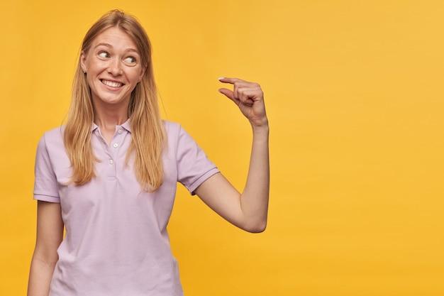 Souriante jolie jeune femme blonde avec des taches de rousseur en t-shirt lavande faisant des gestes avec la main faisant un signe de petite taille avec les doigts sur le mur jaune