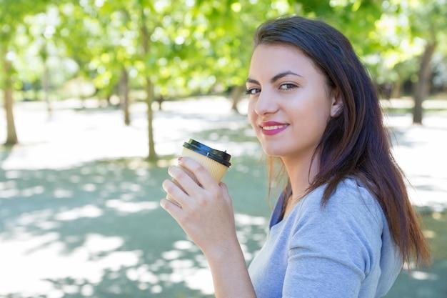 Souriante jolie jeune femme buvant du café dans le parc