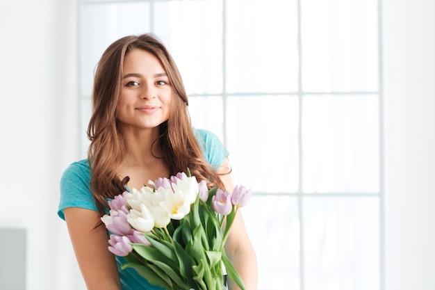 Souriante jolie jeune femme debout et tenant un arrosoir avec un bouquet de fleurs près de la fenêtre