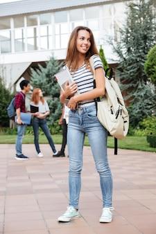 Souriante jolie jeune femme étudiante avec sac à dos marchant à l'extérieur