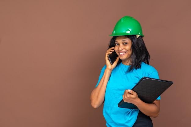 Souriante jolie jeune femme noire entrepreneur faisant un appel téléphonique