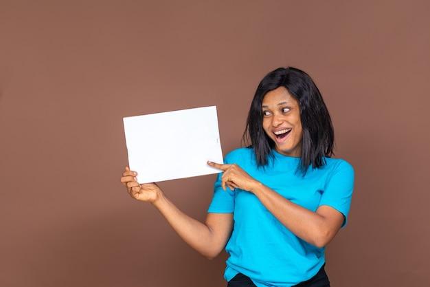 Souriante jolie jeune femme noire tenant une pancarte vide à ses côtés, concept publicitaire