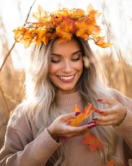 Souriante jolie jeune femme portant des feuilles d'érable diadème jouant avec les feuilles de l'automne
