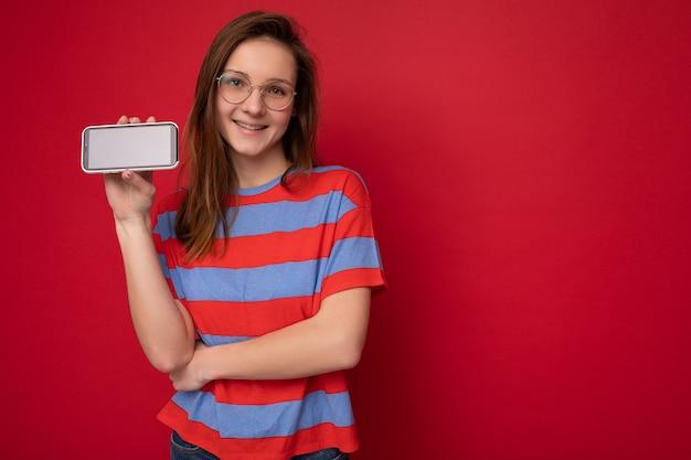 Souriante jolie jeune femme positive à la recherche portant des lunettes optiques et élégant décontracté