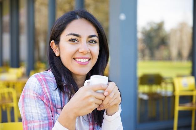 Souriante jolie jeune femme profitant de boire du café au café