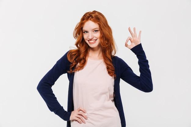 Souriante jolie jeune femme rousse montrant un geste correct.