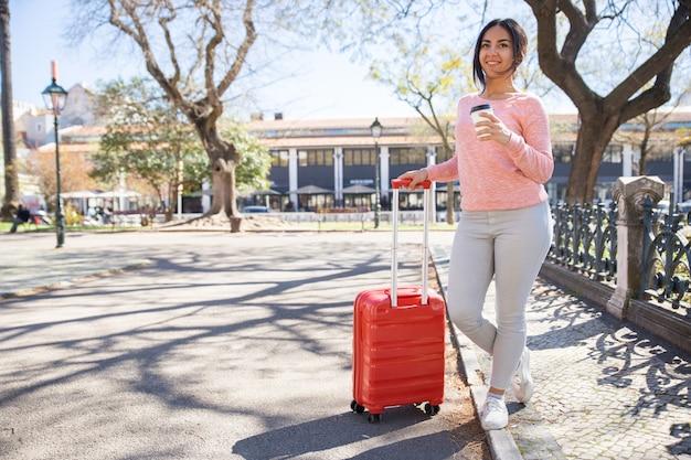 Souriante jolie jeune femme avec valise trolley en plein air