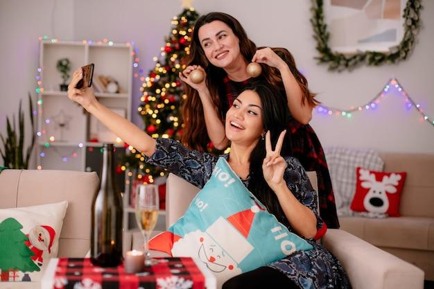 Souriante jolie jeune fille assise sur un fauteuil gestes signe de la victoire et prend selfie avec son ami tenant des ornements de boule de verre profitant du temps de noël à la maison