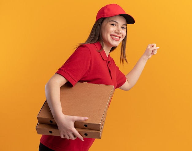 Souriante jolie livreuse en uniforme gardant le poing et tenant des boîtes de pizza sur orange