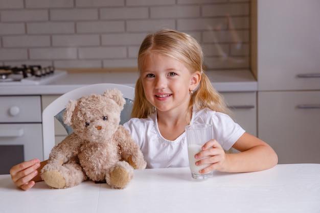 Souriante petite fille blonde buvant du lait dans la cuisine