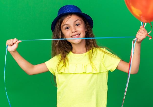 Souriante petite fille caucasienne avec un chapeau de fête bleu tenant des ballons à l'hélium isolés sur un mur vert avec espace de copie