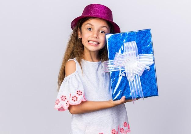 Souriante petite fille caucasienne avec chapeau de fête violet tenant boîte-cadeau isolé sur un mur blanc avec espace copie