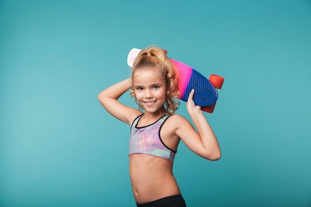 Souriante petite fille sportive jouant avec une planche à roulettes isolée sur mur bleu