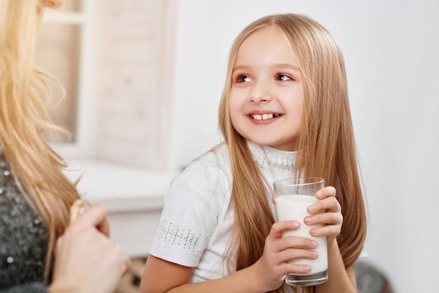 Souriante petite fille tapant du verre de lait près de la mère.