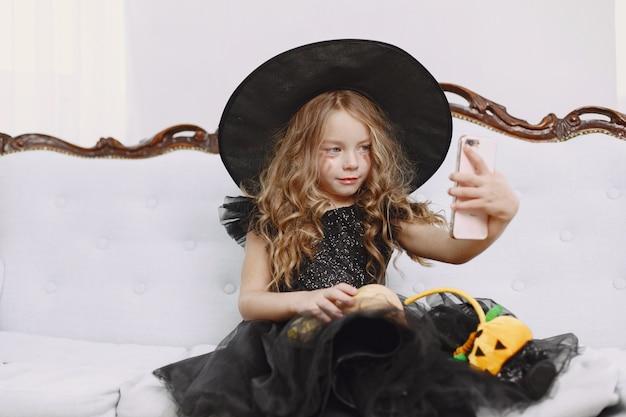Souriante petite sorcière positive positive en costume de carnaval d'halloween