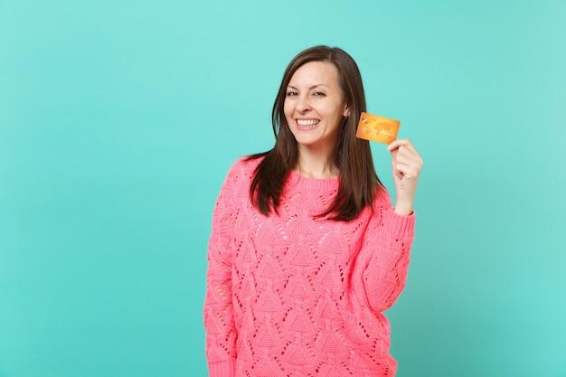 Souriante séduisante superbe jeune femme en pull rose tricoté tenant à la main une carte de crédit isolée sur fond de mur bleu turquoise, portrait en studio. concept de mode de vie des gens. maquette de l'espace de copie.