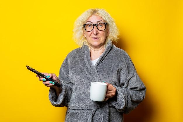 Souriante vieille femme en peignoir gris détient la télécommande et une tasse de café