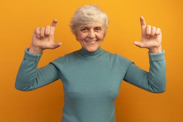Souriante vieille femme portant un pull à col roulé bleu faisant un geste de petite quantité