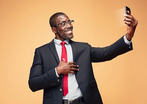Souriez à un autre monde. jeune homme avec un smartphone debout sur fond de studio orange. technologie de reconnaissance faciale sur grille polygonale. concept de cybersécurité, entreprise, travail, éducation.