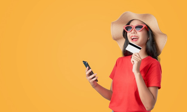 Souriez avec bonheur t-shirt femme asiatique rouge tenant smartphone et carte de crédit, achats en ligne sur orange.