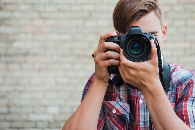 Souriez à la caméra ! jeune homme confiant se concentrant sur vous avec son appareil photo numérique tout en se tenant contre un mur de briques