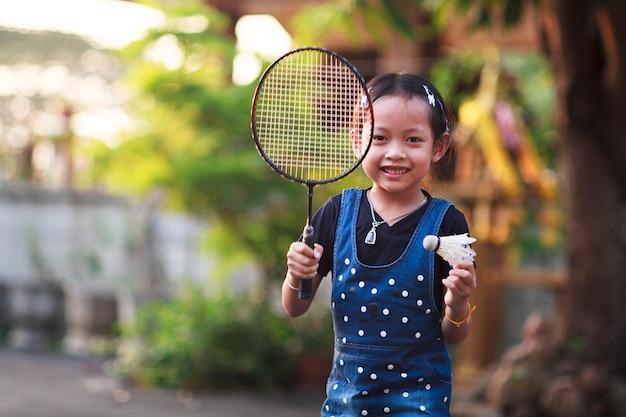 Souriez petite fille jouant au badminton à la maison.