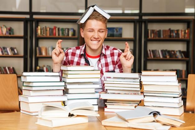 Sourire adolescent assis à la table de la bibliothèque