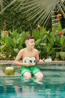 Sourire adolescent métis assis dans la piscine et jouer du ukulélé