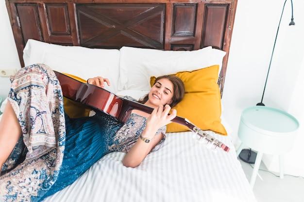 Sourire adolescente allongée sur le lit en jouant de la guitare