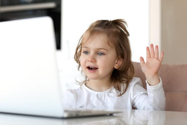 Sourire adorable enfant utilise un chat vidéo d'ordinateur portable pour la communication tout en étant assis à une table à la maison. kid en ligne.