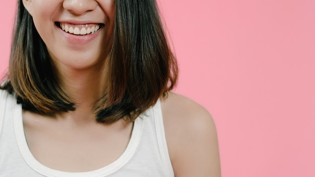 Sourire adorable femme asiatique d'expression positive, sourit largement, vêtue de vêtements décontractés et regardant la caméra sur fond rose.