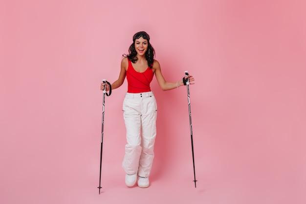 Sourire adorable femme posant avec des bâtons de ski