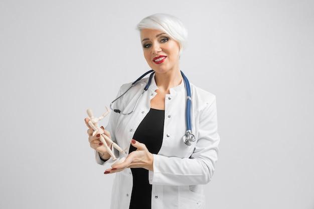 Sourire adulte femme médecin debout tenir dans les bras un modèle de la personne isolée sur