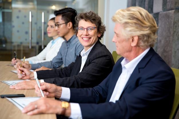 Sourire d'affaires âgé assis à la réunion