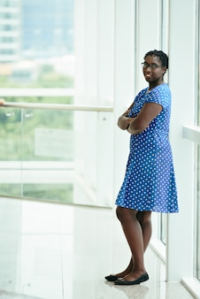Sourire africaine femme en robe bleue à pois s'appuyant sur le cadre de la fenêtre et souriant