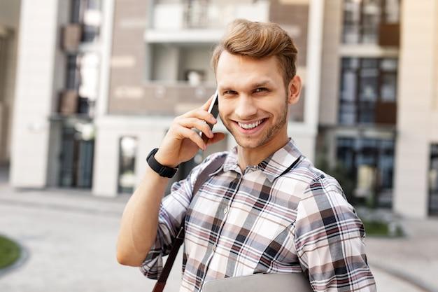 Sourire amical. enthousiaste jeune homme souriant tout en ayant une conversation téléphonique