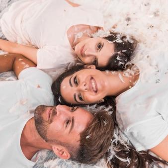 Sourire des amis allongés sur le lit avec des plumes blanches