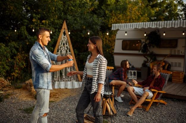 Sourire d'amis reposant sur un pique-nique au camping dans la forêt