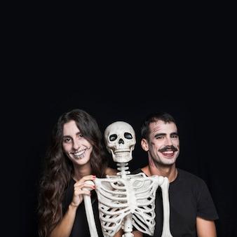 Sourire des amis avec squelette effrayant