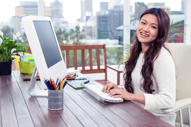 Sourire asiatique femme à l'aide d'ordinateur de bureau