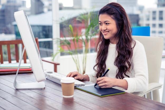 Sourire asiatique femme à l'aide de tableau numérique et ordinateur de bureau