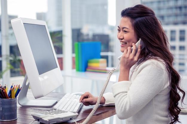 Sourire asiatique femme sur un appel téléphonique à l'aide d'ordinateur de bureau