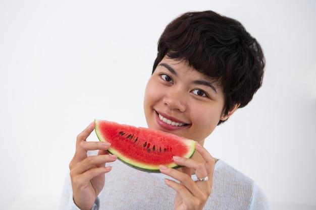 Sourire asiatique femme holding slice of watermelon