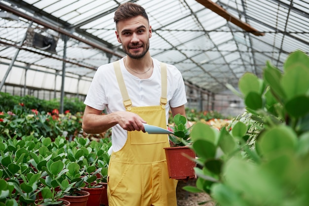 Sourire attrayant barbu travaillant avec des plantes et tenant le vase et la pelle dans les mains.