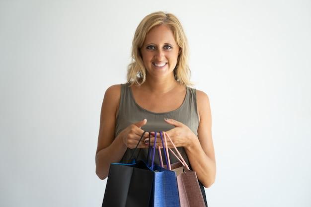 Sourire attrayante femme bronzée tenant des sacs à provisions et en regardant la caméra.